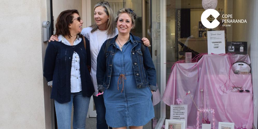 Miembros de la AECC en Peñaranda junto a Carmeli Lagar y el escaparate de su tienda.