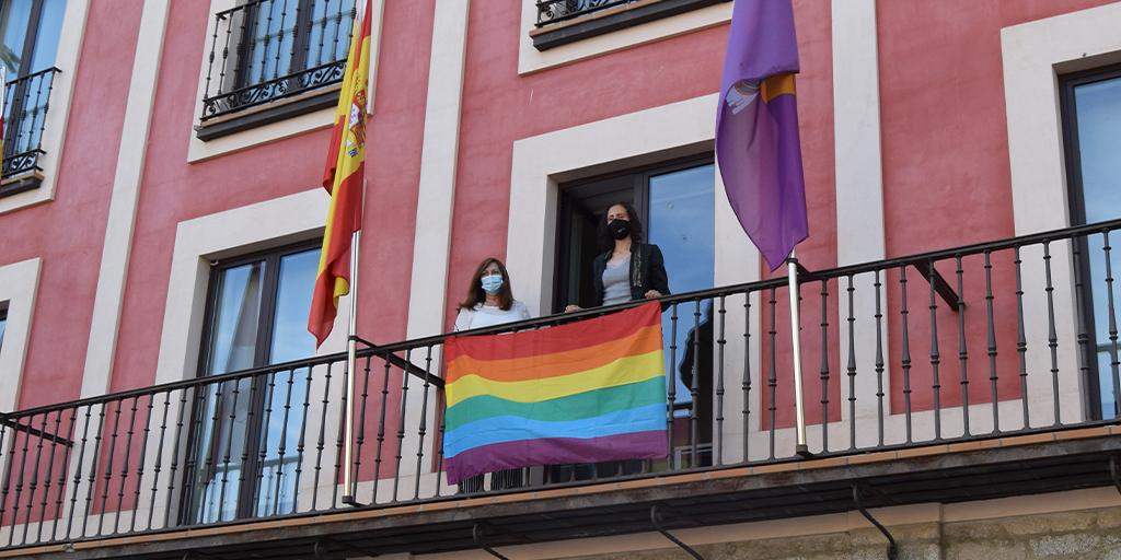 Carmen Ávila y Pilar García colocan la bandera con el arcoiris en el balcón del ayuntamiento