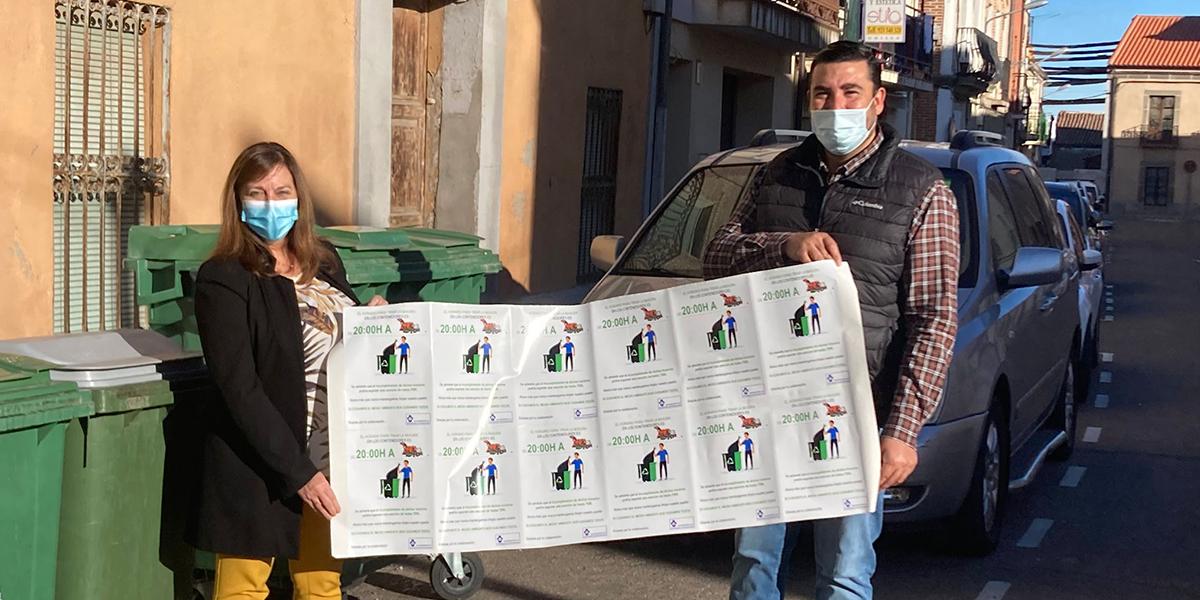 Carmen Ávila y Antonio Poveda con pegatinas informativas sobre el horario de la recogida de basura